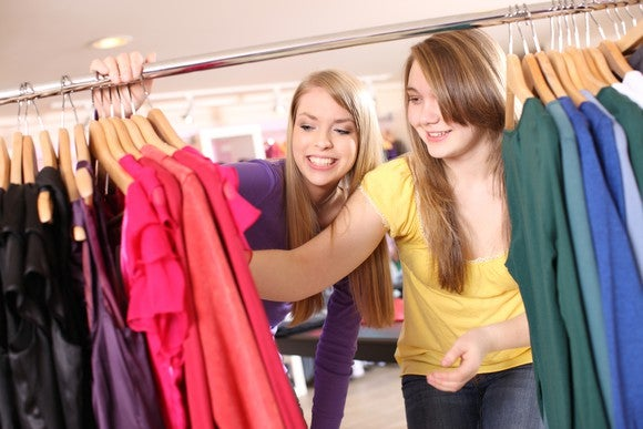 Two teenage women go through clothing.