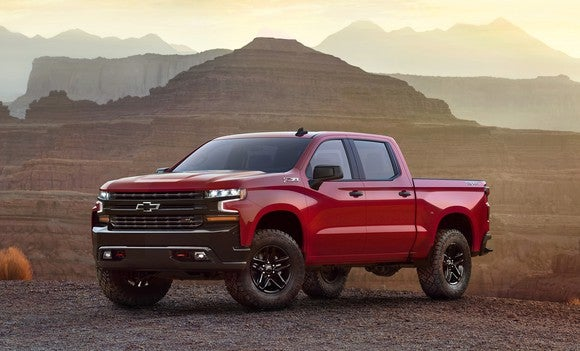A red 2019 Chevrolet Silverado LT Trailboss, a four-door off-road pickup truck, on rugged desert terrain.
