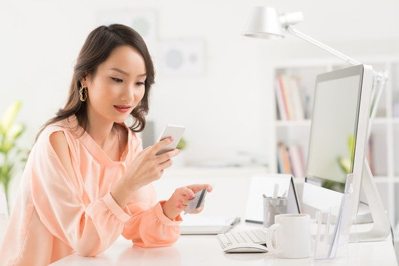 Asian woman shopping online with a credit card