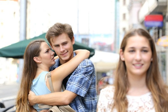 Young man gawks at a passing head-turned while hugging his current girlfriend.