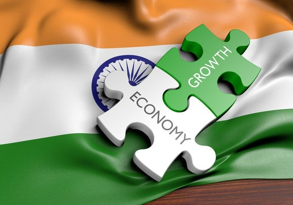 Two jigsaw pieces with economy and growth written on each against a backdrop of the Indian flag.