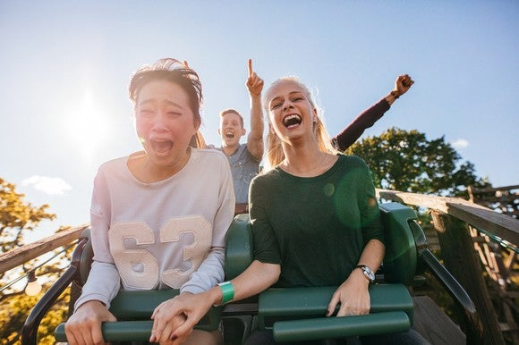 Young adults smiling while riding a roller coaster.