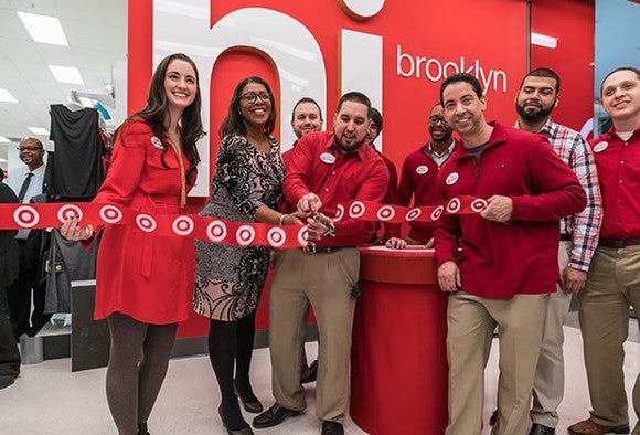 Target employees dressed in red cutting the ribbon for a new Target store grand opening.