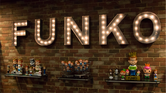 Funko figures on display with a lit FUNKO sign above them.