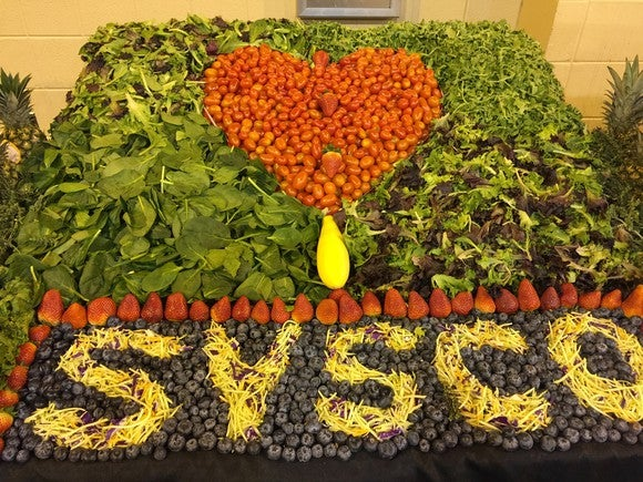 Display spelling Sysco out of greens, fruits, and vegetables.