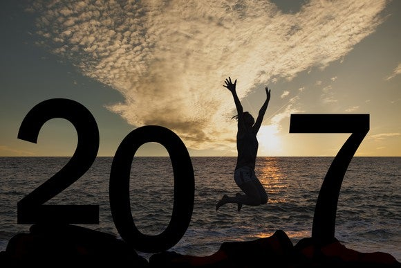 Silhouette of 2017 at sunset in front of ocean with woman jumping where the 1 would be