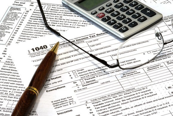 A pen, glasses, and calculator sitting on a 1040 tax form.