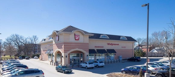 Walgreens store with full parking lot on a sunny day under blue sky.