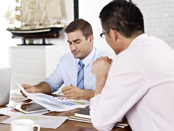 Two professionals reviewing paperwork at a desk