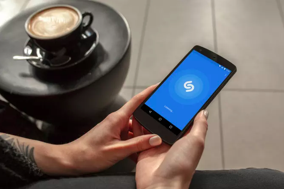 Hands hold an Android phone with Shazam pulled up and a coffee table with a latte stands nearby