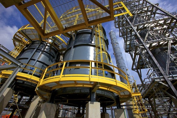 Close-up of refinery equipment, including tall grey storage tanks surrounded by yellow walkways.