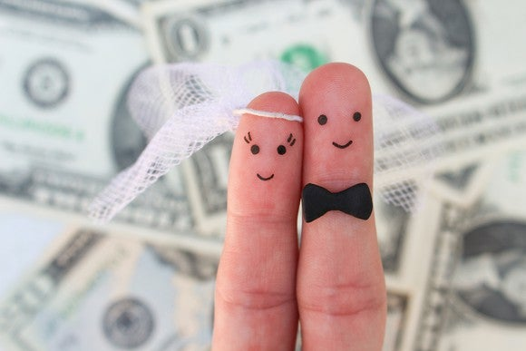 two fingers being held up against background of cash -- they're drawn on so that one, wearing a veil, represents a bride and the other, in a bow tie, represents a groom