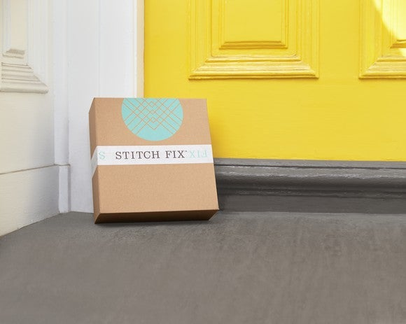 A Stitch Fix box sits on a doorstep against a yellow door.