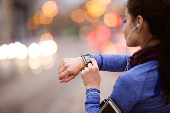 A young woman selects music on her smart watch.