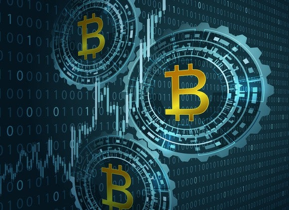 Three bitcoin logos in front of binary code background.