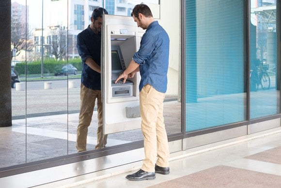 A man withdraws money from an ATM.