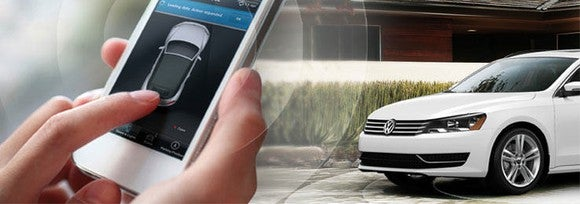 A picture of a white Volkswagen sedan being controlled from a smartphone.