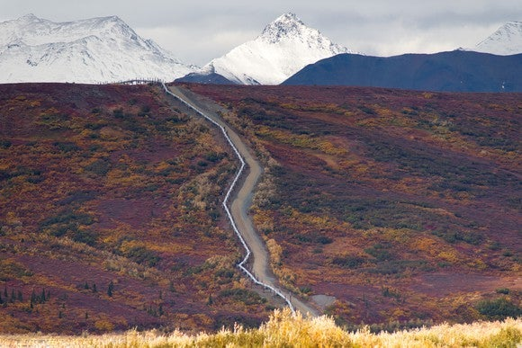 An oil pipeline cutting across a rugged mountain.