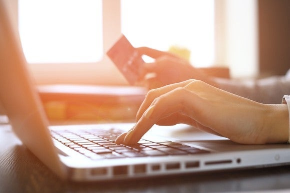 A woman's hand hovers over a keyboard while the other holds credit card.