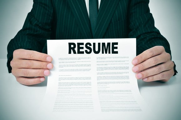 torso shown of man in suit holding a resume in front of him