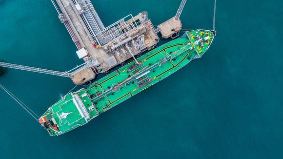 An overhead view of an LNG shipping vessel being loaded at an export terminal.