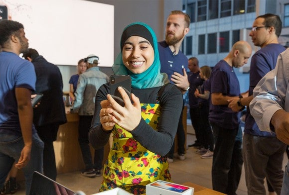 A woman holding an iPhone X inside of an Apple store.