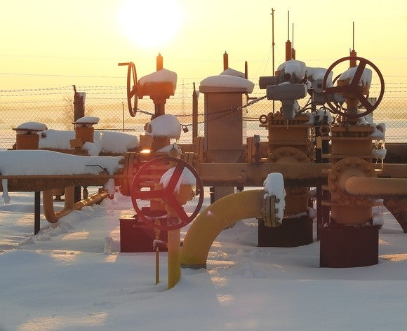 Snow covered pipes coming from a natural gas field with the sun in the distance.