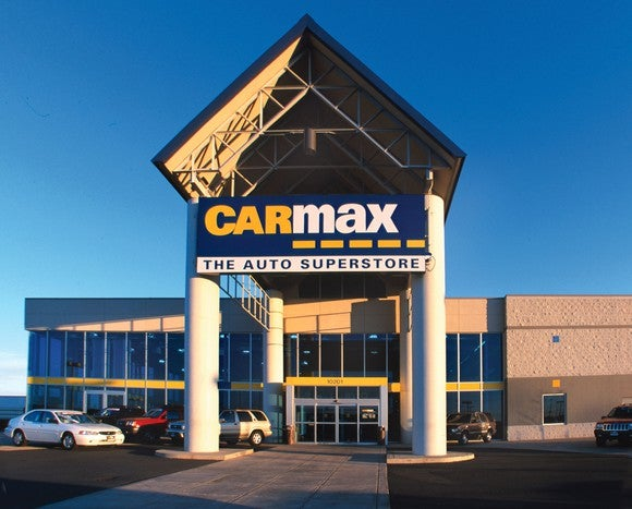 CarMax dealership location with large entryway cover and several cars parked in front of the building.