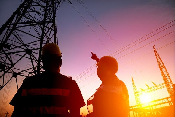 Two utility workers looking up at power transmission lines.