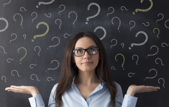 A woman standing in front of a chalkboard covered by question marks shrugs her shoulders.