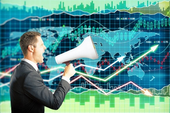 A businessman speaks into a megaphone while standing in front of a monitor showing the world and stock price charts moving in different directions.