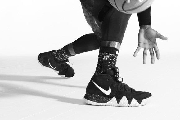 A pair of Nike basketball shoes shown with a pair of hands dribbling a basketball.