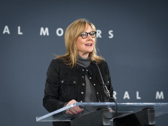 Mary Barra speaking at a podium in front of a backdrop with General Motors' logo.