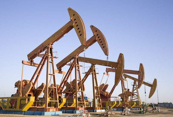 A row of pump-style oil wells in a desert landscape