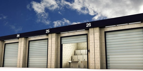 A row of self-storage units, with boxes visible inside one open unit.