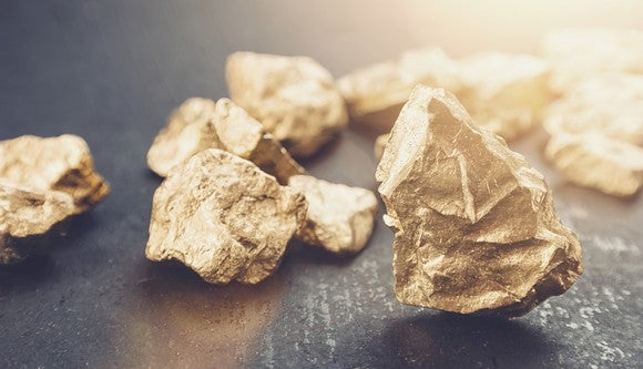 Large gold nuggets on a black metal background.