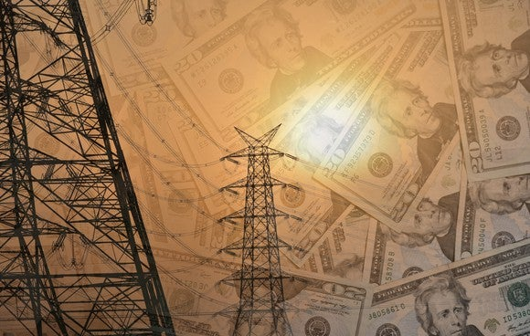 Electric transmission lines with high power wires and U.S. dollars in the background.