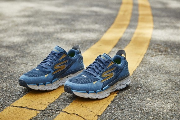 Pair of Skechers sneakers on a double yellow line in the middle of the road.