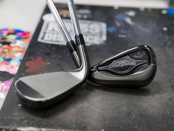 Two Callaway-branded irons, with heads shown on a black surface.