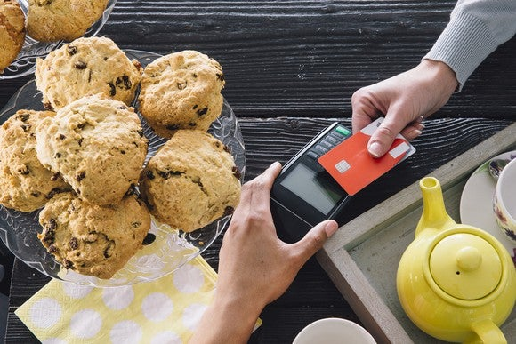A person paying for an item at a bakery counter by holding a chip credit card over a card reader terminal.