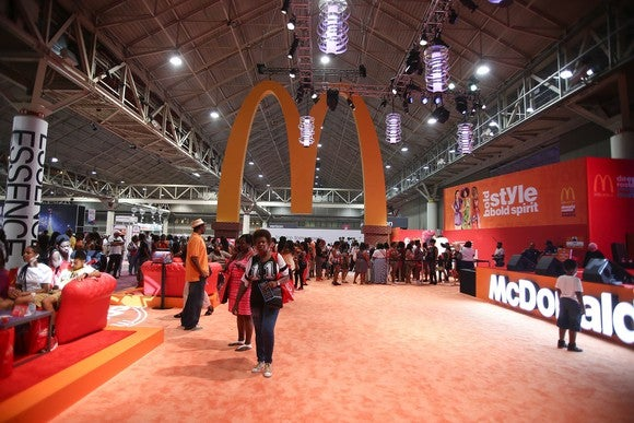 Golden Arches hanging from the ceiling of a convention hall over an empty carpet, with McDonald's booth at right.