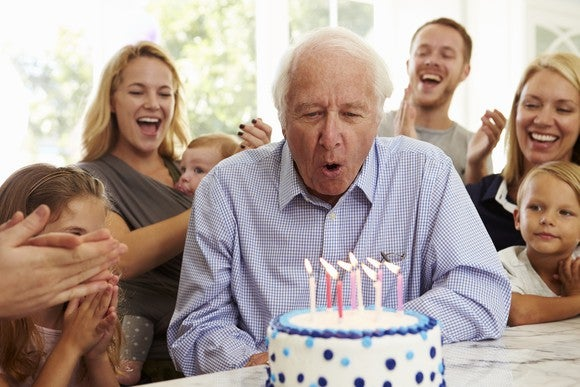 Senior male blowing out candles on a birthday cake with people of various ages clapping behind him