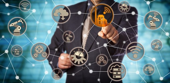 A businessman stands in the middle of a network of IoT devices.