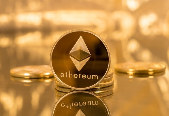 "A gold-and-dark colored coin with ""ethereum"" on it, in front of a golden background."