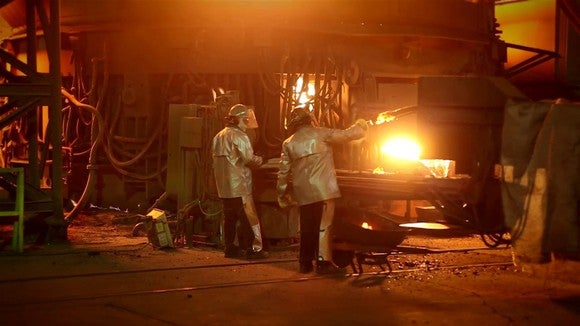 Two workers in heat-protection suits doing metal work in front of a glowing furnace.