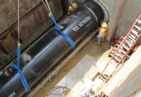 A black steel water pipe is installed underground on a construction site.