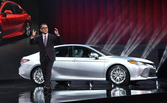 Toyoda is shown on an auto-show stage with a silver 2018 Camry sedan.