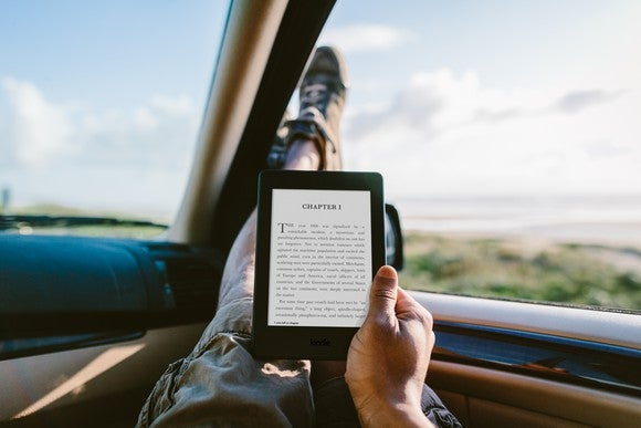A man reading on a Kindle Paperwhite in his car
