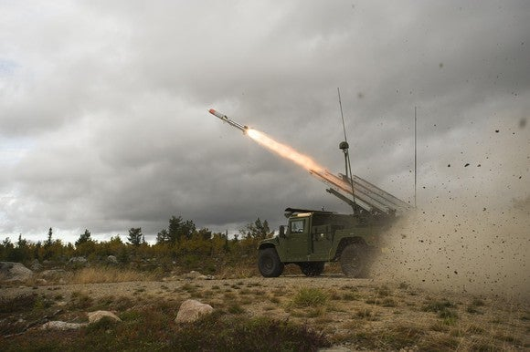 Missile launching from a truck-based platform in a desert battlefield on a cloudy day.