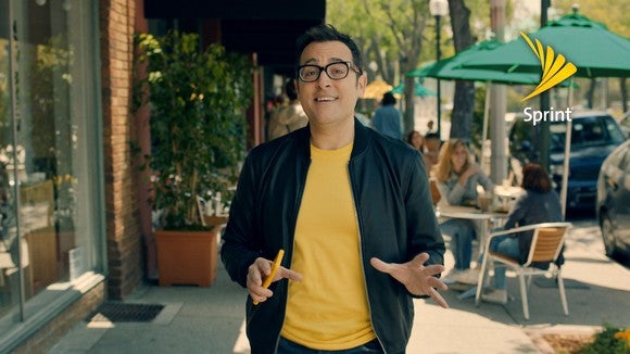 Sprint spokesman Paul Marcarelli walks down a sidewalk with people dining behind him.